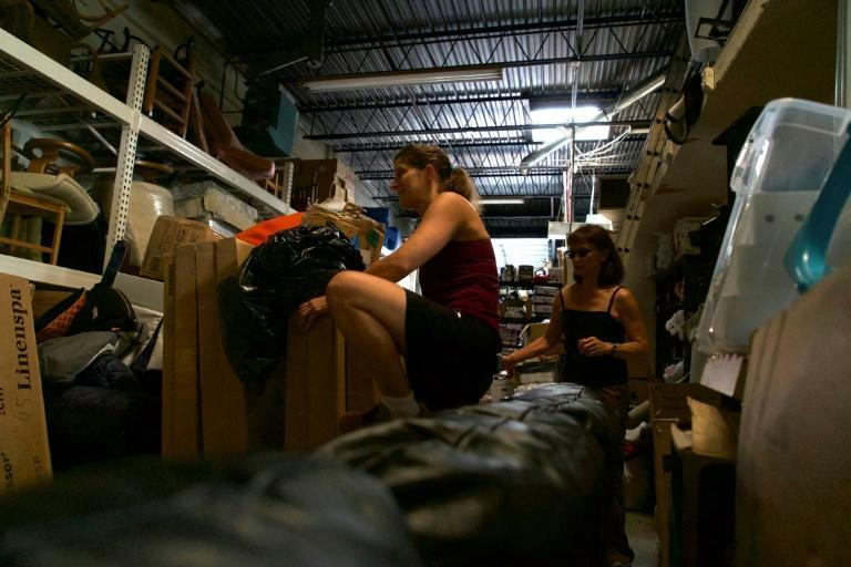 Laura Thompson Osuri (L), director of Homes Not Borders, scales shelves and rummages through boxes at a Maryland warehouse to collect home goods to help furnish apartments for new Afghan arrivals (AFP/Bastien INZAURRALDE)