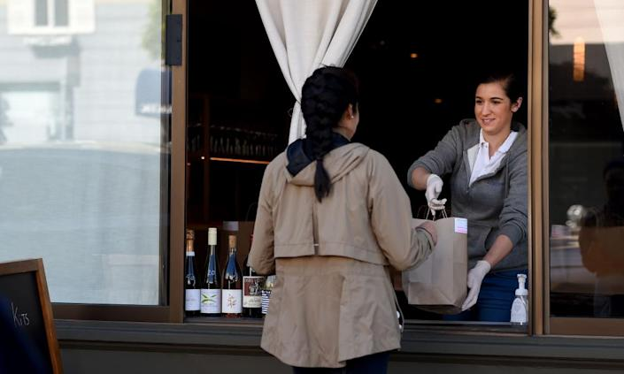 """<span class=""""element-image__caption"""">An employee for Atelier Crenn restaurant hands a takeout order to a customer in San Francisco, California.</span> <span class=""""element-image__credit"""">Photograph: Josh Edelson/AFP via Getty Images</span>"""