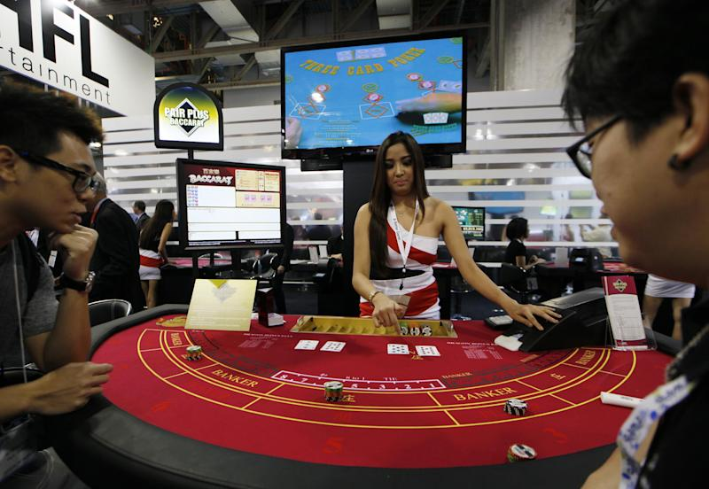 In this photo taken on Thursday, May 23, 2013, an attendant demonstrates the game of baccarat on a baccarat gaming table during the Global Gaming Expo Asia in Macau. Almost all of Macau's $38 billion in gambling revenue last year - six times more than the Las Vegas Strip - came from card game, much of it from Chinese high-rollers betting borrowed money and dwarfing the takings from slots, blackjack or roulette. Wherever you go in the former Portuguese colony, you'll see chain-smoking Chinese gamblers crowded around baccarat tables as players peel back their cards, hoping their luck will give them a good hand. (AP Photo/Kin Cheung)