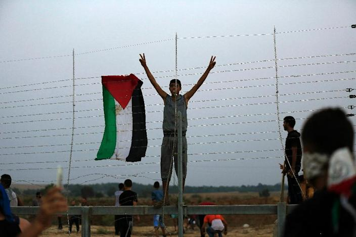 "A Palestinian youth flashes the ""V"" for victory sign as he stands inside Israeli territory after protestors tore down a section of a border fence between Israel and the Gaza Strip during clashes on October 12, 2015, east of Bureij in central Gaza (AFP Photo/Mohammed Abed)"