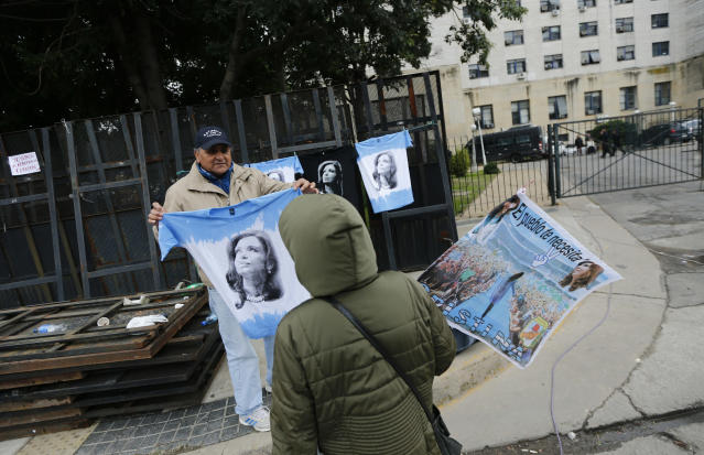 A man sells T-shirts featuring Argentina's former President Cristina Fernández outside the federal court where she went on trial in Buenos Aires, Argentina, Tuesday, May 21, 2019. Fernández appeared in court Tuesday for the first in a series of corruption trials ahead of a planned run for the vice presidency. (AP Photo/Marcos Brindicci)