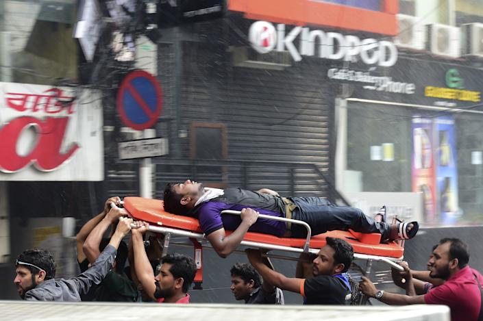 A Bangladeshi survivor is taken to hospital after being rescued by firefighters from a burning office building in Dhaka on March 28, 2019.  (Photo: Munir Uz Zaman/AFP/Getty Images)