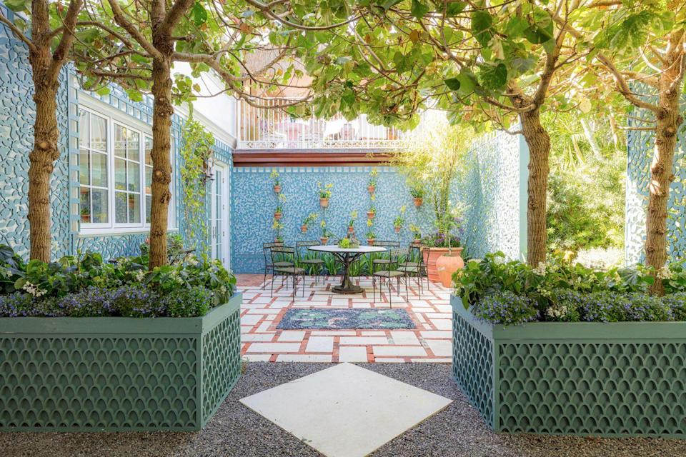 "<p>If the word ""lattice"" conjures images of white crisscrossed wood, think again: SMI's Jorge Sanchez, Claudia Visconti, Brian Vertesch, and John Lubischer covered the exterior walls behind the house in a leaf-patterned lattice which, painted in Benjamin Moore's Aegean Teal, gives the effect of an outdoor wallpaper. Oversized planters with towering trees provide shade and delineate several outdoor spaces, proving that <strong>outdoor rooms can be just as thoughtfully arranged as their interior counterparts </strong>(especially in sunny Florida!).<br></p>"