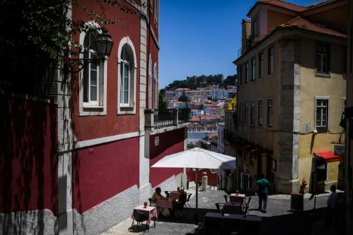 People sit at a terrcae bar in downtown Lisbon -- a slew of new virus cases in and around the city have seen the Portuguese government impose new restrictions