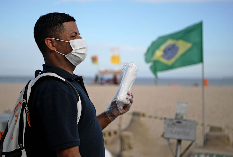 A street vendor sells face masks as a preventive measure against the spread of the new coronavirus, COVID-19, on Copacabana beach in Rio de Janeiro, Brazil, on March 16, 2020. - Beach lifeguards were asking beachgoers to avoid congregating in large numbers on one of the world's most famous beaches to prevent the spread of the coronavirus outbreak. (Photo by Carl DE SOUZA / AFP) (Photo by CARL DE SOUZA/AFP via Getty Images)