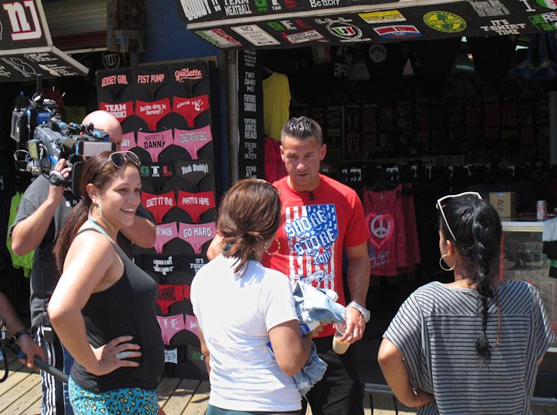 "Michael ""The Situation"" Sorrentino speaks with Michelle Diaz, left, Patricia Garcia,  center, and Lisa Rodriguez, right, all of Philadelphia, on the boardwalk in Seaside Heights, N.J. during a break in taping of an episode of the MTV series ""Jersey Shore,"" Friday, July 15, 2011. A new nationwide poll finds the show's depiction of a group of hard-drinking, foul-mouthed 20-somethings has not hurt New Jersey's national image, and may help it in some small ways. (AP Photo/Wayne Parry)"