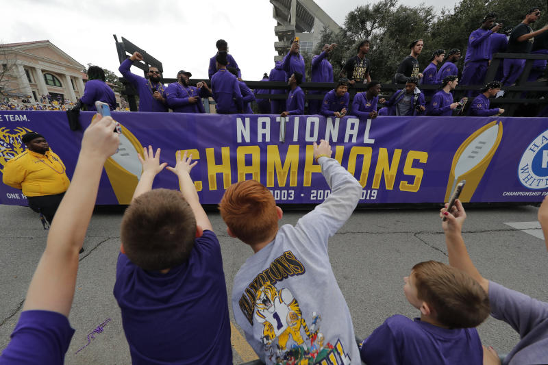LSU fans cheer as players ride on floats during a parade celebrating LSU's NCAA college football championship, Saturday, Jan. 18, 2020, on the LSU campus in Baton Rouge, La. (AP Photo/Gerald Herbert)