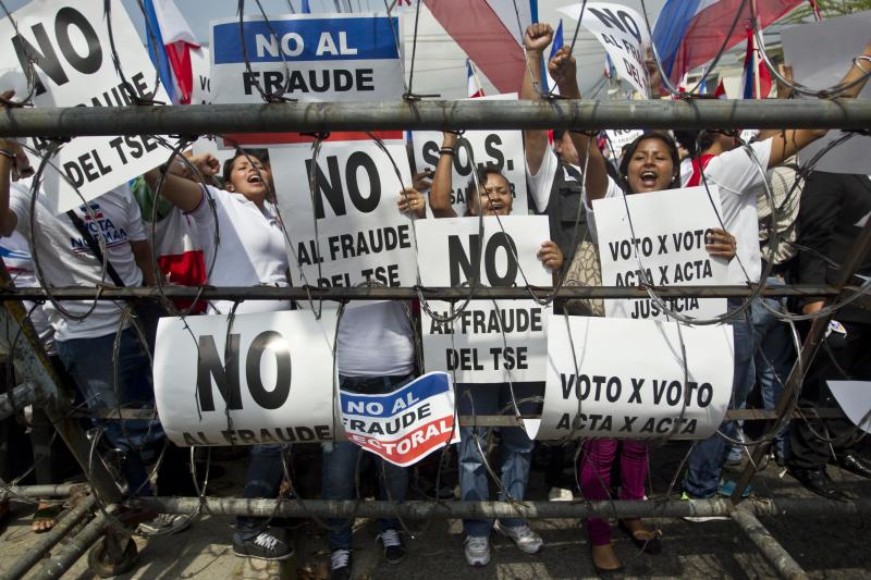 "Supporters of Norman Quijano, Nationalist Republican Alliance presidential candidate, many holding posters that read in Spanish; ""No to electoral fraud,"" demand a vote recount of Sunday's runoff election during a protest, in San Salvador, El Salvador, Tuesday, March 11, 2014. El Salvador's too-close-to-call election has raised competing claims of victory from the two candidates; Salvador Sanchez Ceren of the Farabundo Marti National Liberation Front and Quijano. (AP Photo/Esteban Felix)"