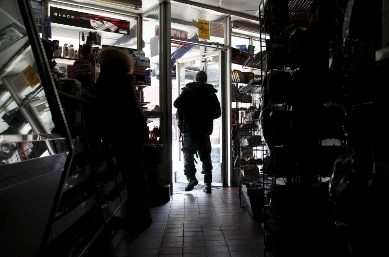 A customer shops at Andy's Deli in the dark, Wednesday, Oct. 31, 2012, in New York. Days after superstorm Sandy hit, businesses both big and small are facing a tough choice,  to reopen or stay closed.  (AP Photo/Seth Wenig)