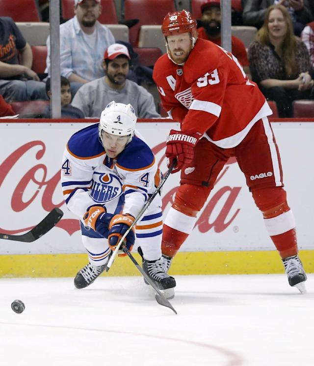 Detroit Red Wings' Johan Franzen (93), of Sweden, tries to keep Edmonton Oilers' Taylor Hall (4) off the puck during the first period of an NHL hockey game Friday, March 14, 2014, in Detroit. (AP Photo/Duane Burleson)