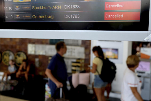 Passengers pass by a flights screen showing two cancelled flights of Thomas Cook at Larnaca airport in the eastern Mediterranean island of Cyprus, Monday, Sept. 23, 2019. The collapse of Thomas Cook will strike a major blow to the Cypriot tourism industry. (AP Photo/Petros Karadjias)