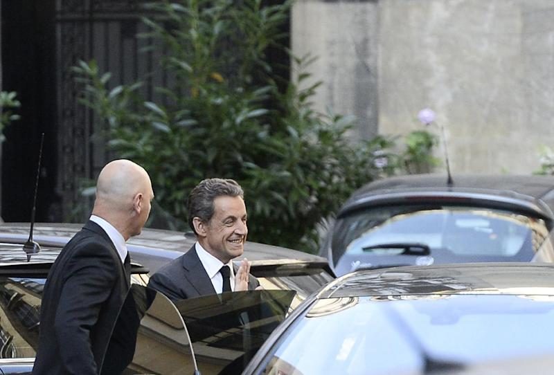 Former French President Nicolas Sarkozy (R) smiles as he gets into a car outside his offices in central Paris on July 2, 2014