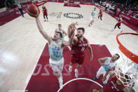 Slovenia's Luka Doncic (77) grabs a rebound ahead of Germany's Danilo Barthel (22) during a men's basketball quarterfinal round game at the 2020 Summer Olympics, Tuesday, Aug. 3, 2021, in Saitama, Japan. (AP Photo/Charlie Neibergall, Pool)