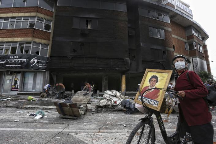 A woman walks past La Luna hotel that was burned and looted Monday night during a protest against tax reform in Cali, Colombia, Tuesday, May 4, 2021. Colombia's finance minister resigned on Monday following five days of protests over a tax reform proposal that left at least 17 dead. (AP Photo/Andres Gonzalez)