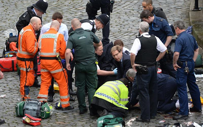 Conservative MP Tobias Ellwood (centre) helps emergency services battling to save the life of Pc Keith Palmer  - PA