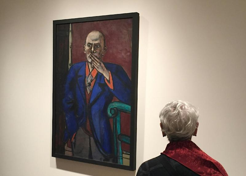 """A woman looks at """"Self-Portrait in Blue Jacket"""" (1950) during a press preview for the exhibition called """"Max Beckmann in New York"""" at the Metropolitan Museum of Art in New York on October 17, 2016 (AFP Photo/Thomas Urbain)"""