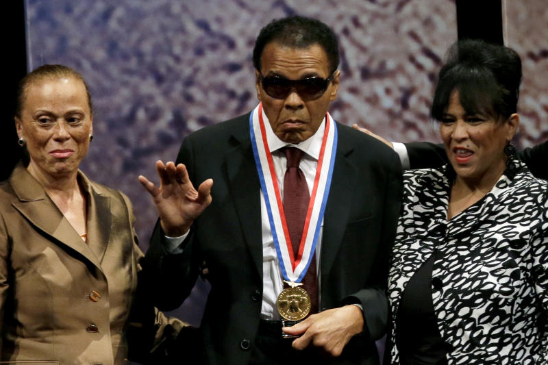 Retired boxing champion Muhammad Ali, center, waves alongside his wife Lonnie Ali, left, and his sister-in-law Marilyn Williams, right, after receiving the Liberty Medal during a ceremony at the National Constitution Center, Thursday, Sept. 13, 2012, in Philadelphia. The honor is given annually to an individual who displays courage and conviction while striving to secure liberty for people worldwide. (AP Photo/Matt Slocum)