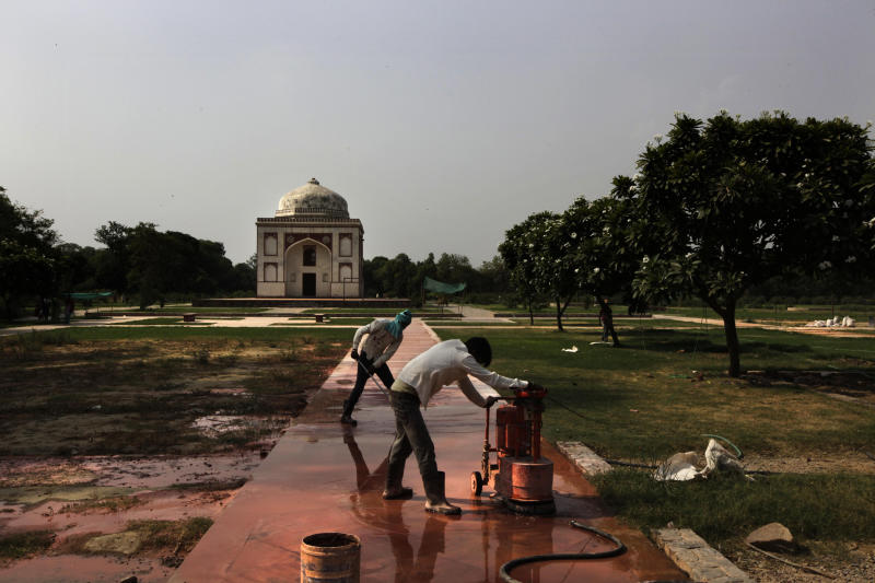 In this Wednesday, June 5, 2013 photo, Indian laborers work to renovate the Sunder Nursery, a 100 acre field founded by British colonists to grow experimental plants, in New Delhi, India. The renovation is intended to serve as the catalyst for an even more ambitious project: the creation of a mammoth, iconic park that would rival New York's Central Park as a refuge from urban chaos. It would be 1,200 acres, considerably larger than Central Park. It would encompass one of the most impressive collections of medieval Islamic monuments, anchored by the grandiose tomb of Emperor Humayun, a 16th Century prototype for the Taj Mahal. (AP Photo /Manish Swarup)