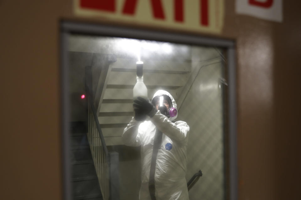 Safety Director Tony Barzelatto sprays disinfectant in a stairwell in Co-op City in the Bronx borough of New York, Wednesday, May 13, 2020. Regular cleanings occur throughout the common areas of the buildings while the heavy disinfecting occurs in response to specific incidents, in this case reports of two coronavirus cases on the same floor. Within the Bronx, almost no place has been hit as hard as Co-op City. (AP Photo/Seth Wenig)
