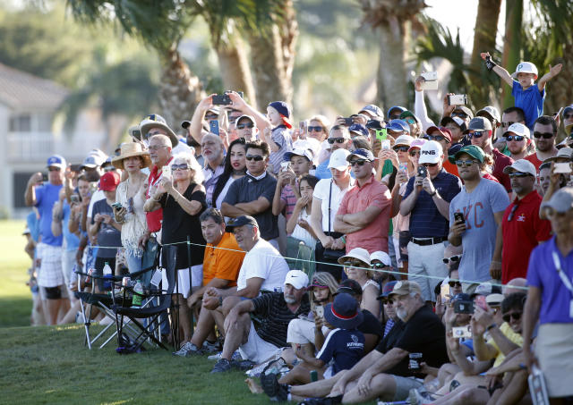 Golf fans watch as Tiger Woods plays the 18th hole during the final round of the Honda Classic golf tournament, Sunday, Feb. 25, 2018, in Palm Beach Gardens, Fla. (AP Photo/Wilfredo Lee)