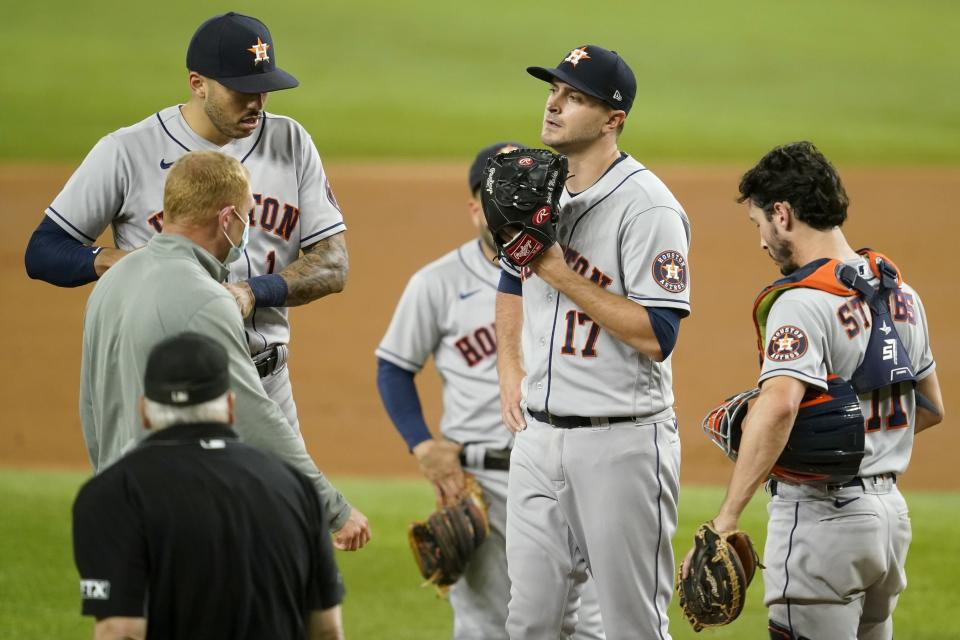 Houston Astros starting pitcher Jake Odorizzi (17) stands on the mound as umpire Larry Vanover, a team staff member, left, Carlos Correa, left rear, and Garrett Stubbs (11) pay a visit in the second inning of a baseball game against the Texas Rangers, in Arlington, Texas, Monday, Sept. 13, 2021. Odorizzi left the game with an unknown injury. (AP Photo/Tony Gutierrez)