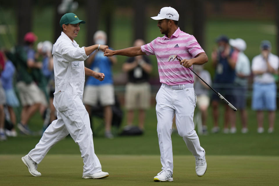 Xander Schauffele is congratulated by his caddie Austin Kaiser after an eagle on the 15th hole during the third round of the Masters golf tournament on Saturday, April 10, 2021, in Augusta, Ga. (AP Photo/Matt Slocum)