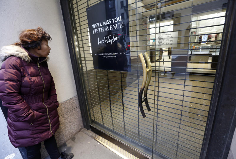 A woman pauses to read a farewell sign from outside Lord & Taylor's flagship Fifth Avenue store which closed for good, Wednesday, Jan. 2, 2019, in New York. (AP Photo/Kathy Willens)