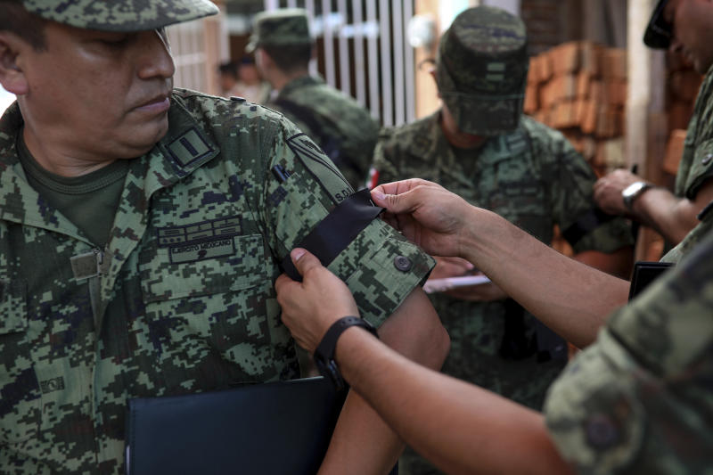 """A Mexican army officer is given a black ribbon on his sleeve during the wake for Alfredo Gonzalez Munoz, a soldier that died during a massive gun battle in the city of Culiacan between drug cartel gunmen and members of the army and the police, in Veracruz, Mexico, Saturday, Oct. 19, 2019. The gunfight in the city of roughly 800,000 residents was triggered Thursday by an attempt to arrest Ovidio Guzman, son of convicted drug lord Joaquin """"El Chapo"""" Guzman Loera, in response to a U.S. request for extradition. (AP Photo/Felix Marquez)"""