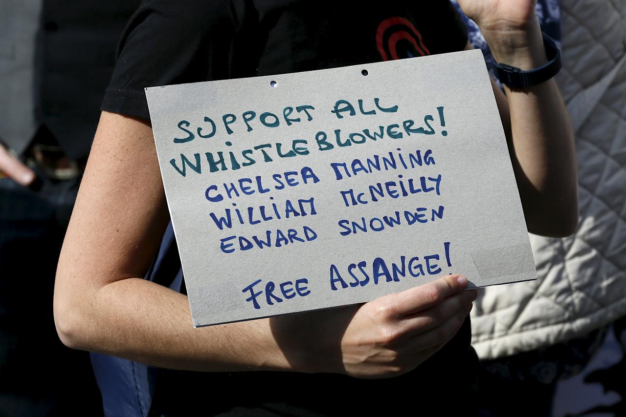 A supporter of Wikileaks founder Julian Assange holds a placard during a gathering outside the Ecuador embassy in London, Britain June 19, 2015. REUTERS/Stefan Wermuth