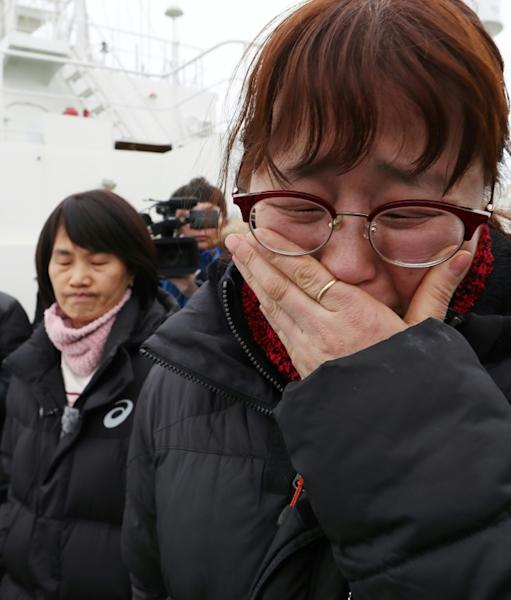 South Korean relatives watch as the damaged Sewol ferry is raised between two barges during a salvage operation off the southwestern island of Jindo, on March 23, 2017