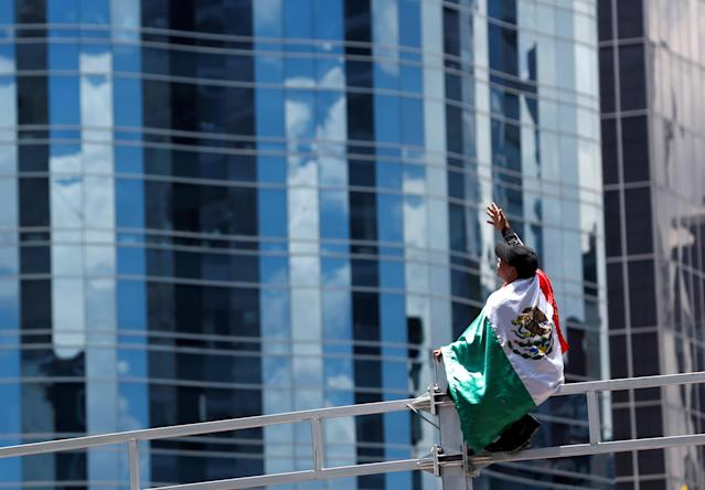 Soccer Football - FIFA World Cup - Group F - Germany v Mexico - Mexico City, Mexico - June 17, 2018 - A Mexican fan celebrates at the Angel of Independence monument. REUTERS/Gustavo Graf
