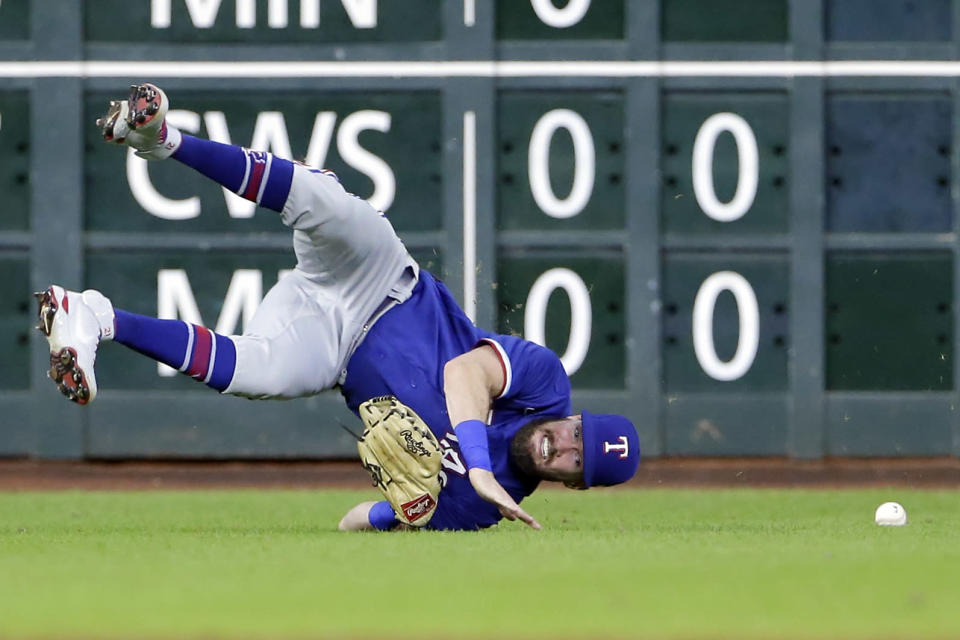 Texas Rangers left fielder David Dahl tumbles on a diving catch-attempt on a hit by Houston Astros' Michael Brantley during the third inning of a baseball game Friday, July 23, 2021, in Houston. (AP Photo/Michael Wyke)