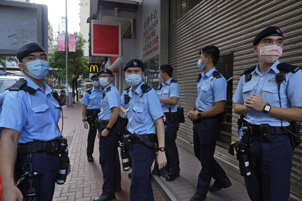 """Police officers stand guard at a street during a protest against an election committee that will vote for the city's leader in Hong Kong Sunday, Sept. 19, 2021. Hong Kong's polls for an election committee that will vote for the city's leader kicked off Sunday amid heavy police presence, with chief executive Carrie Lam saying that it is """"very meaningful"""" as it is the first election to take place following electoral reforms. (AP Photo/Vincent Yu)"""