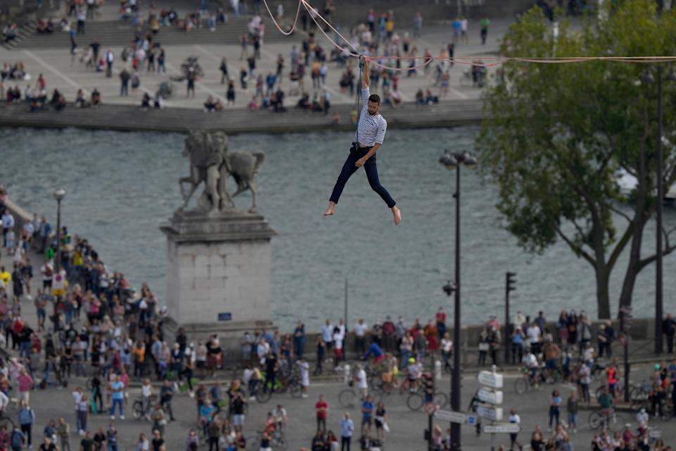 French slackliner Nathan Paulin performs on the second time on a 70-meter-high slackline between the Eiffel Tower and the Chaillot Theater and faces a crowd of thousands.