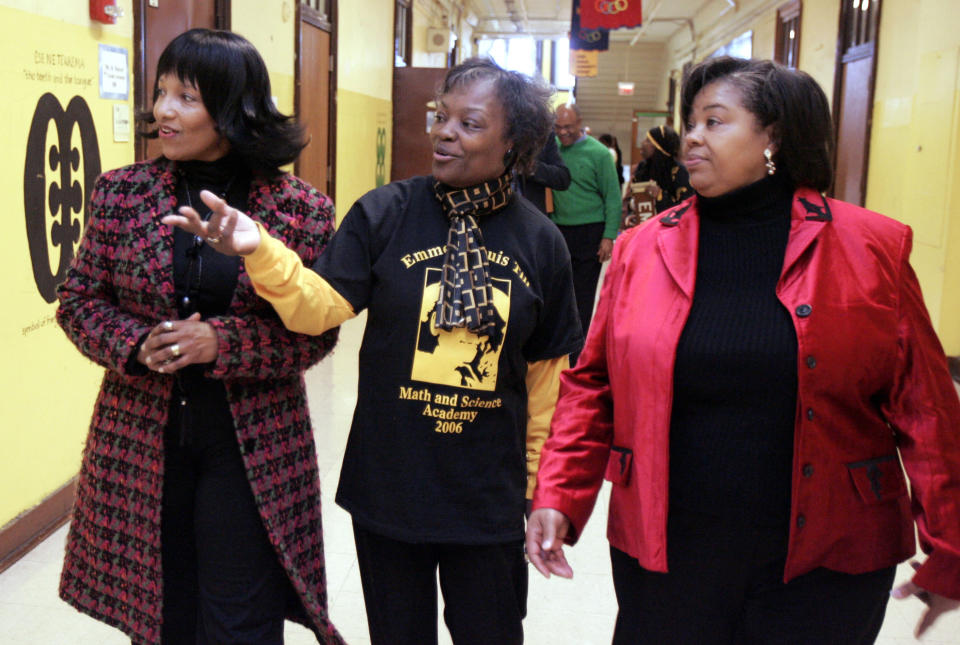 FILE - In this Feb 24, 2006, file photo, Deborah Watts, left, and Ollie Gordon, right, both cousins of Emmett Till, accompany Principal Mary Rogers as they walk through a hallway at Emmett Louis Till Math & Science Academy, in Chicago, honoring the 14-year-old former student. Till's lynching galvanized the civil rights movement. George Floyd, the Black Minneapolis man's killing by police sparked a worldwide call for racial justice. The deaths of Till and Floyd are separated by more than six decades, but their families feel a deep connection in their grief. (AP Photo/M. Spencer Green, File)