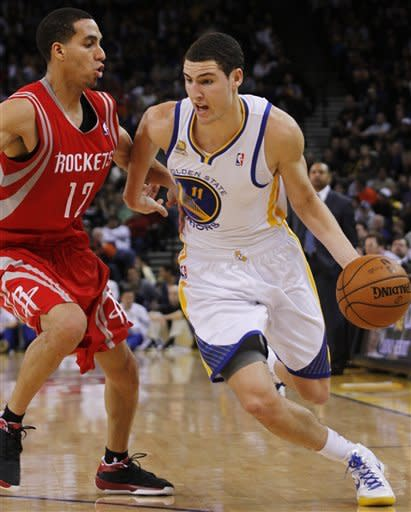 Golden State Warriors' Klay Thompson drives for the basket past Houston Rockets' Kevin Martin during the second half of an NBA basketball game, Sunday, Feb. 12, 2012, in Oakland, Calif. The Warriors beat the Rockets 106-97. (AP Photo/George Nikitin)