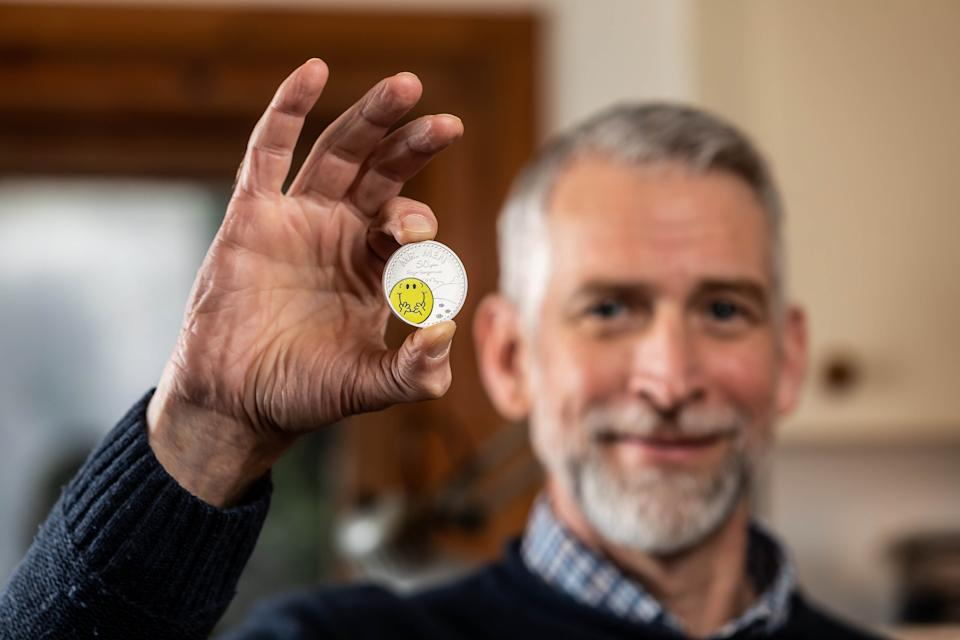 Adam Hargreaves, son of Mr Men and Little Miss creator Roger Hargreaves, holds The Royal Mint's new £5 Mr Happy coin, which launches today to celebrate 50 years of the characters. Photo: PA Media
