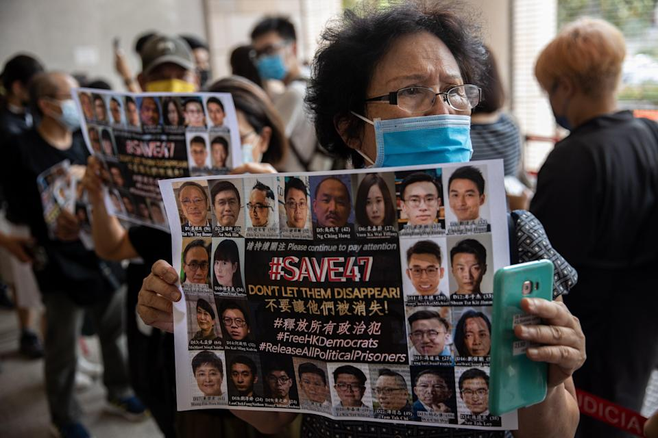 A supporter holds a poster of pro-democracy figures on trial under the new national security law for participating in an unofficial primary in 2020 (EPA)