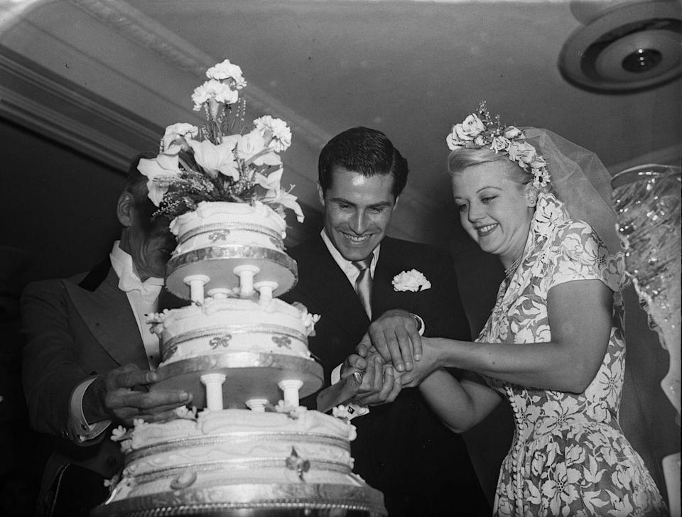 <p>The British actress and star of <em>Murder, She Wrote</em>, Angela Lansbury, cuts the cake with her husband, producer Peter Shaw, on their wedding day, August 13, 1949. This was the second marriage for her, but it was his first and only. They remained married until his death in 2003. </p>