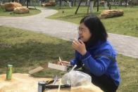 "In this photo taken April 14, 2020 and released by Melanie Wang, Zhang Zhan eats a meal at a park during a visit to Wuhan in central China's Hubei province. A Chinese court on Monday sentenced the former lawyer who reported on the early stage of the coronavirus outbreak to four years in prison on charges of ""picking fights and provoking trouble,"" one of her lawyers said. (Melanie Wang via AP)"