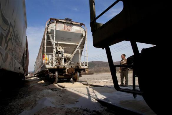 Chuck Compton, a conductor at Wellsboro & Corning Railroad in Wellsboro, Pennsylvania, couples railcars filled with sand to be transloaded for energy companies drilling natural gas wells in the area April 3, 2010.