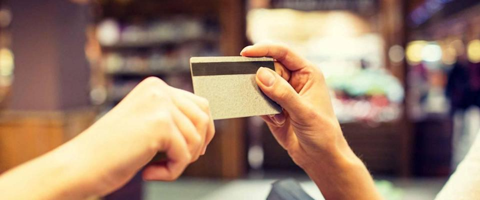 Sale, shopping, payment, consumption and people concept - close up of hands giving credit card to cashier in market or mall