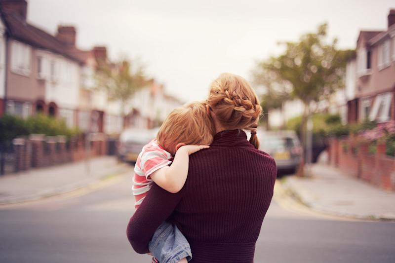 A young boy being held by his mother with his head resting on her shoulder, looking down a suburban street.