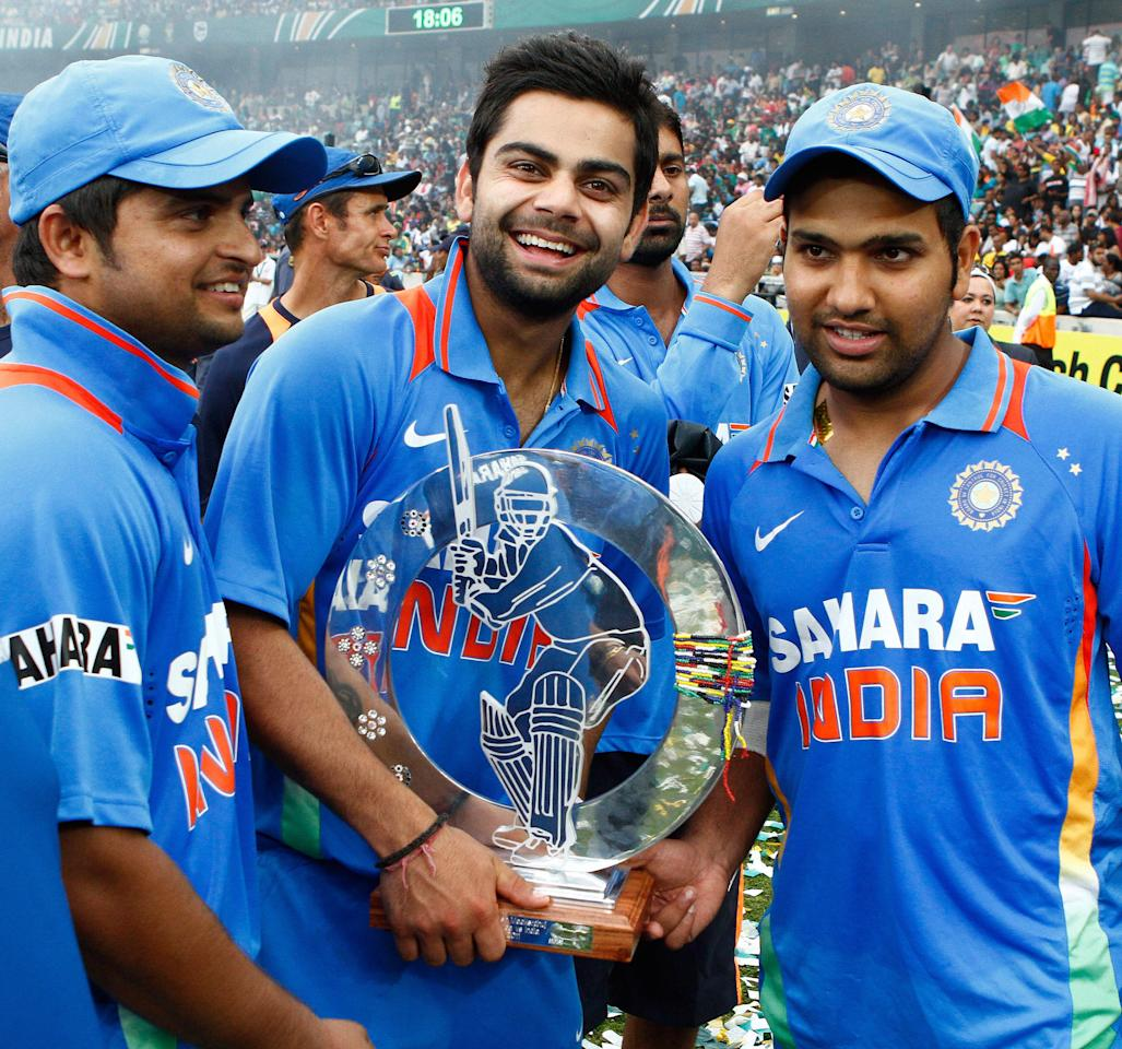 DURBAN, SOUTH AFRICA - JANUARY 09:  (L-R) Suresh Raina, Virat Kohli and Rohit Sharma of India celebrate with the winners trophy after the Standard Bank Pro20 international match between South Africa and India at Moses Mabhida Stadium on January 09, 2011 in Durban, South Africa. (Photo by Anesh Debiky/Gallo Images/Getty Images)