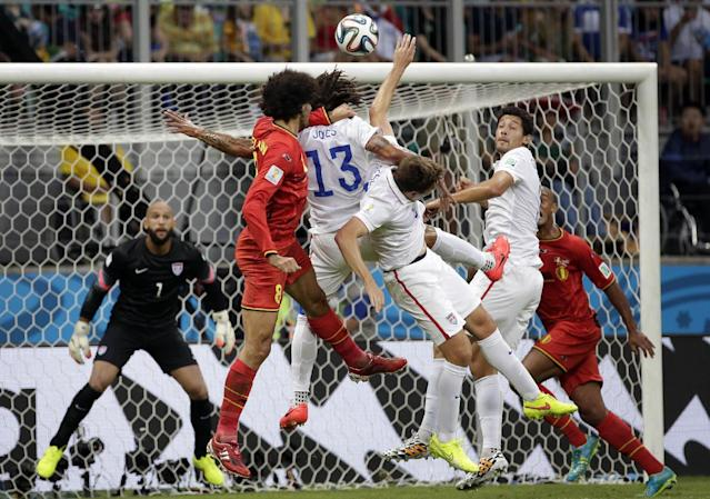 Belgium's Marouane Fellaini, second from left, goes for a header against United States' Jermaine Jones (13) as United States' goalkeeper Tim Howard, left, eyes the ball during the World Cup round of 16 soccer match between Belgium and the USA at the Arena Fonte Nova in Salvador, Brazil, Tuesday, July 1, 2014. (AP Photo/Felipe Dana)