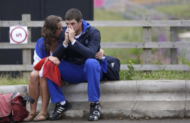 Rower Julien Bahain, of France's men's double sculls team, is comforted by his girlfriend after his team finished fifth in a semifinal race and failed to advance to the final in Eton Dorney, near Windsor, England, at the 2012 Summer Olympics, Tuesday, July 31, 2012. (AP Photo/Chris Carlson)