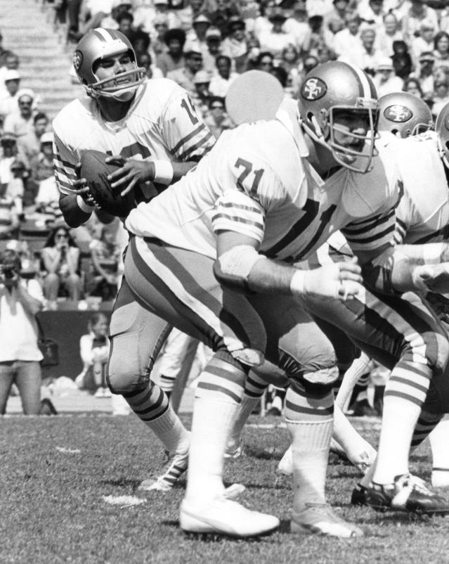 CORRECTS SPELLING TO FAHNHORST, NOT FAHNHURST - This Oct. 2, 1977, photo provided by the NFL shows San Francisco 49ers tackle Keith Fahnhorst (71) blocking for quarterback Jim Plunkett (16) as he drops back to pass against the Los Angeles Rams, at Los Angeles Memorial Coliseum. Former star San Francisco 49ers tackle Keith Fahnhorst has died at 66. The team said Friday he died Tuesday, June 12, 2018. No cause was given. (NFL Photos via AP)