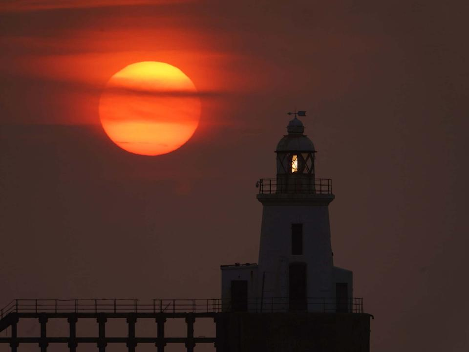 The sun rises behind Blyth East Pier Lighthouse in Northumberland on 11 August 2020: PA