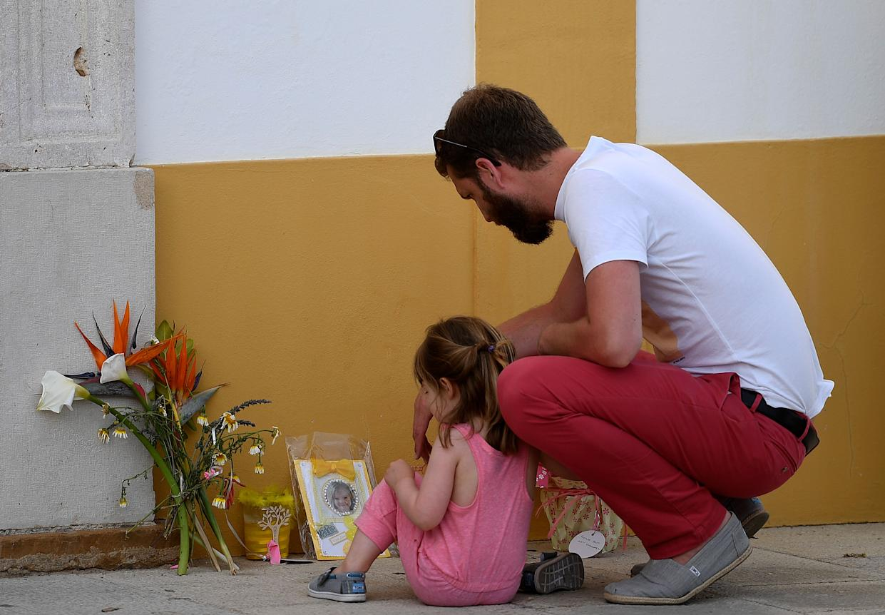 """A man and a little girl look at flowers, candles and a photograph of """"Maddie"""", placed on the street as a tribute to missing child Madeleine McCann, outside the church in Praia da Luz near Lagos on May 3, 2017 on the 10th anniversary of her disappearance. Madeleine McCann (Maddie) disappeared in Praia da Luz on May 3, 2007. Portuguese police closed the case in 2008 before reopening it five years later. / AFP PHOTO / FRANCISCO LEONG        (Photo credit should read FRANCISCO LEONG/AFP/Getty Images)"""