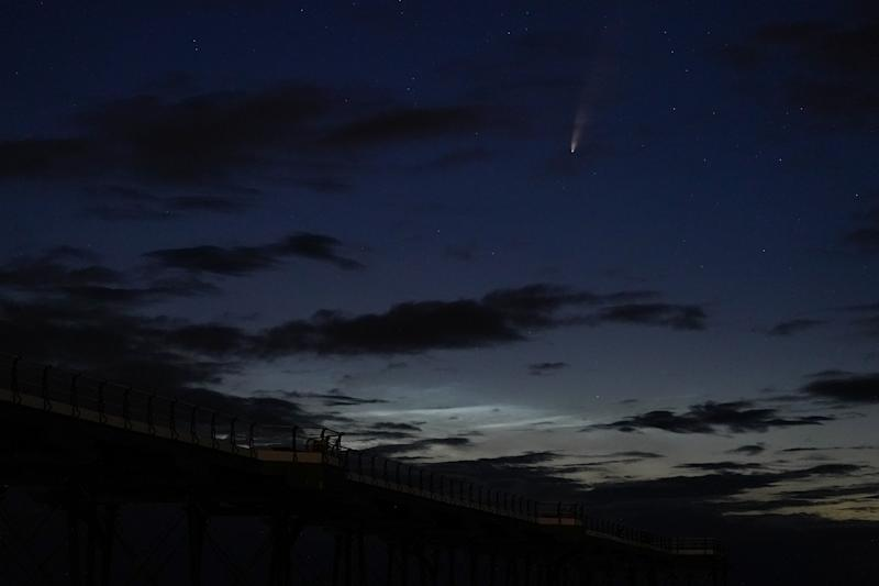 SALTBURN BY THE SEA, ENGLAND - JULY 13: Comet Neowise is visible in the night sky above Saltburn pier on July 13, 2020 in Saltburn By The Sea, England. Comet Neowise, officially called C/2020 F3, first appeared towards the end of March. It brightened as it reached its closest approach to the Sun, inside the orbit of Mercury late last week. Comet Neowise is one of the few naked-eye comets of the 21st Century. It will be visible in the northern hemisphere just before sunrise and after sunset. Throughout July, Neowise is moving westwards across the sky. The comet will come closest to Earth on July 23, though it will still be about 64 million miles (103 million km) away. (Photo by Ian Forsyth/Getty Images)
